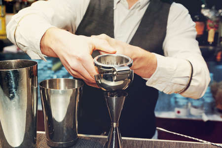 squeezing: Bartender is squeezing citrus juice in jigger, toned image
