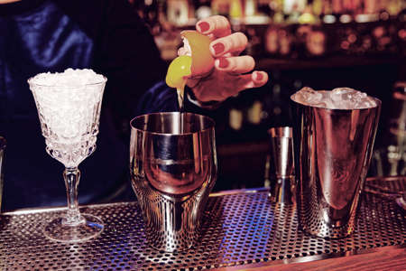 adding: Bartender is adding egg yolk to the glass, toned Stock Photo