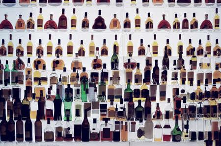 botella de whisky: Varias botellas de alcohol en un bar, luz de fondo, todos los logos eliminado, tonificado