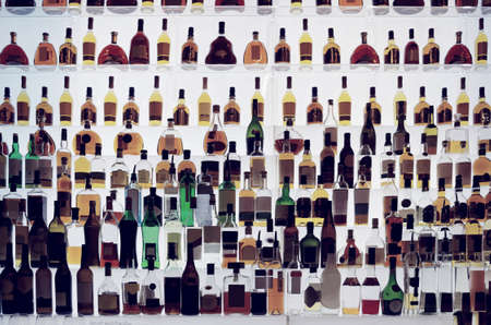 bar counter: Various alcohol bottles in a bar, back light, all logos removed, toned
