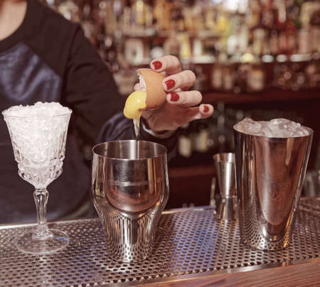 adding: Female bartender is adding egg yolk to the glass, toned