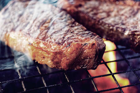 grille: Two pieces of striploin steak on grill, outdoor picnic, toned