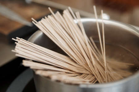 buckwheat noodle: Buckwheat noodles being cooked on induction stove Stock Photo