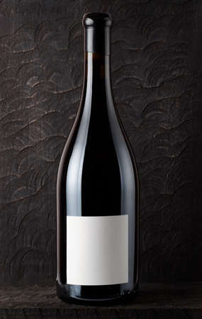 syrah: Bottle of Shiraz red wine, old wooden surface in background Stock Photo