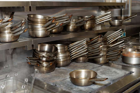 stainless steel range: Lots of stainless steel pans, professional kitchen equipment