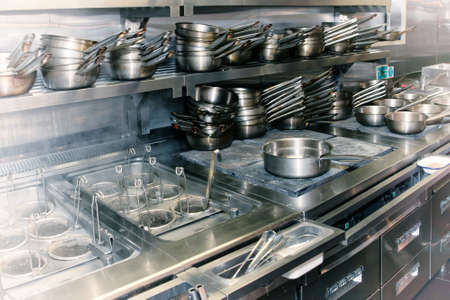 stainless steel range: Typical kitchen of a restaurant shot in operation, toned image