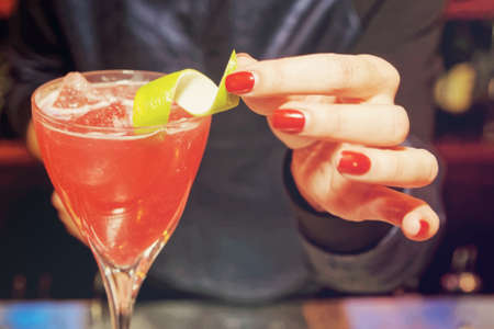 lady hand: Female bartender is decorating a cocktail with lime zest, toned image
