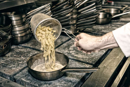 sautee: Chef is cooking pasta at commercial kitchen, toned image