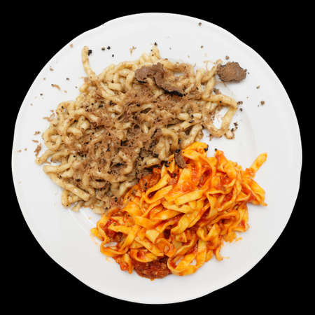 Pastas with black truffle and tomato sauce isolated on black background