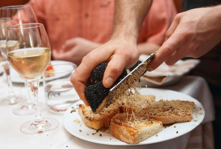 Waiter is grating black truffle on bread with olive oil