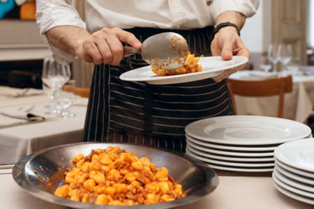 servings: Chef is putting gnocchi with meat in plates