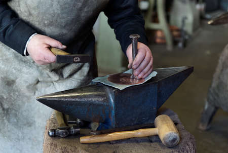 forger: Old smith is chieseling a copper sheet in workshop, making pattern