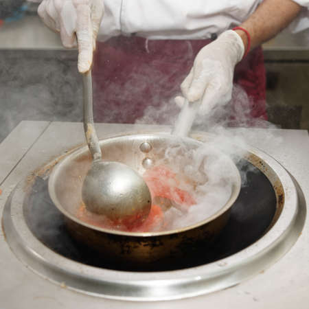 friture: Chef is stirring vegetables with sour sauce in wok