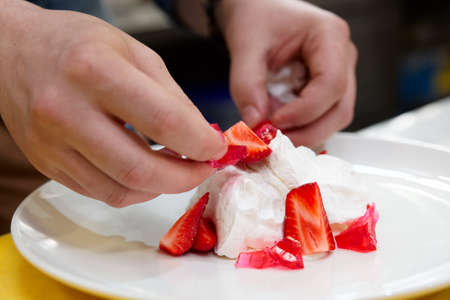 decoracion de pasteles: El cocinero está cocinando postre merengue con fresas y mermelada