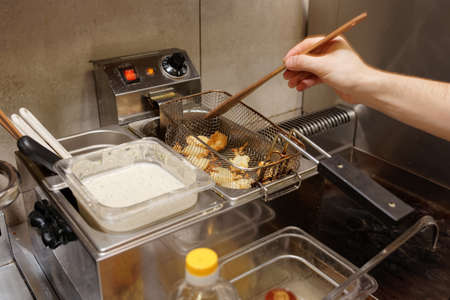 friture: Chef is making nuggets, cheap fast food restaurant Stock Photo