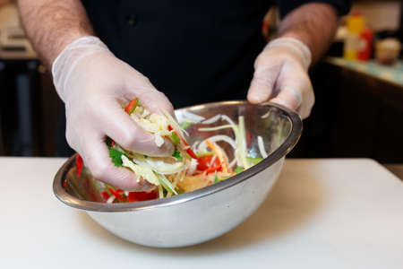 Chef is cooking a vegetarian salad at professional kitchen