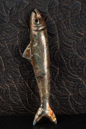 single animal: Handmade clay fish against black wood surface