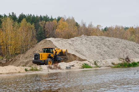 earthmover: Earth-mover and a large pile of bank sand