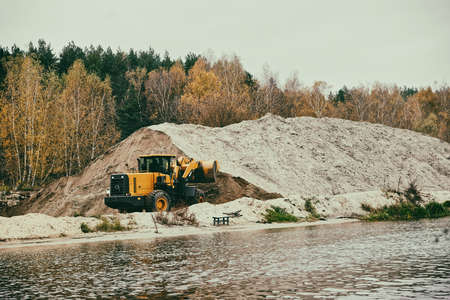 earthmover: Earth-mover and a large pile of bank sand, toned image