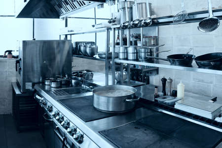 stainless steel range: Professional kitchen interior, crock on stove, toned image