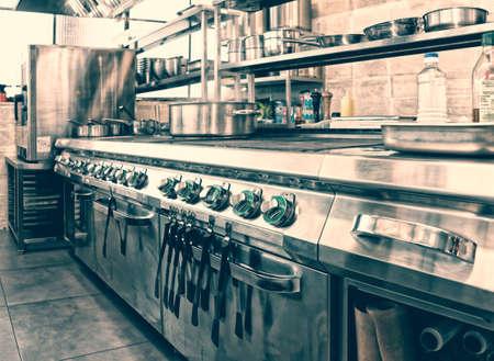 Interior de la cocina profesional, cántaro en la estufa, imagen de tonos Foto de archivo - 67047875