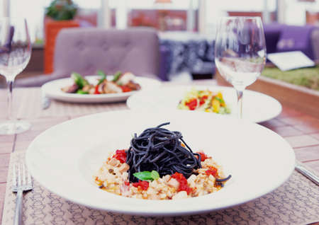 restaurant dining: Black squid ink pasta with seafood and other dishes on restaurant table, toned image Stock Photo