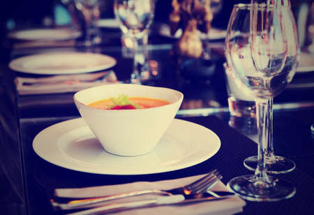 gaspacho: Dish with pumpkin soup on set restaurant table, toned image