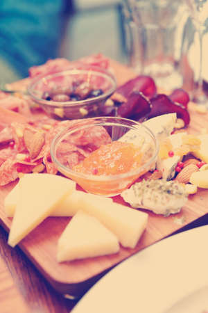 Cheese and sausage platter with nuts and citrus jam, toned image Stock Photo