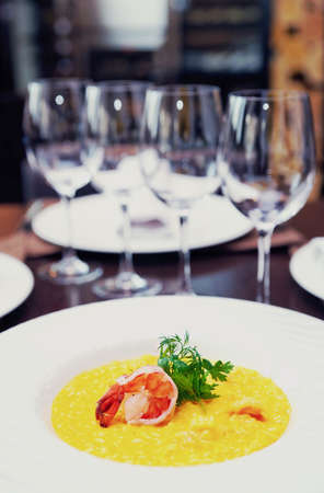 Risotto with shimp on arranged restaurant table, toned image Stock Photo