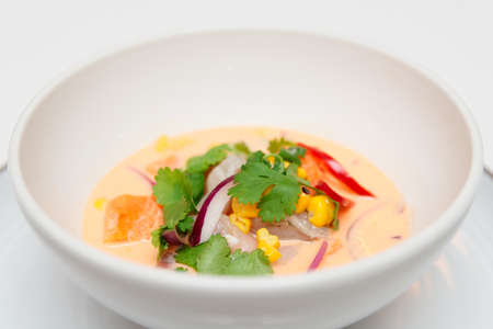 gastronomy: Sea bass ceviche with pumpkin, cilantro, corn and onion in deep plate, close-up