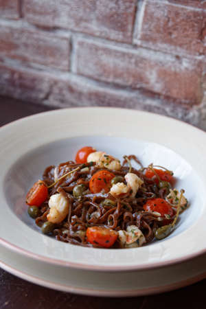 alcaparras: Rye pasta with capers and prawns in white porcelain plate against brick wall Foto de archivo
