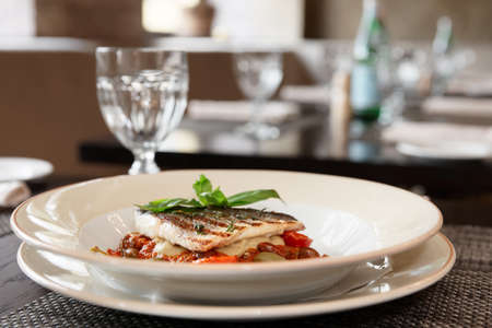Sea bass fillet with tomato sauce and capers, place setting of a restaurant Stock Photo