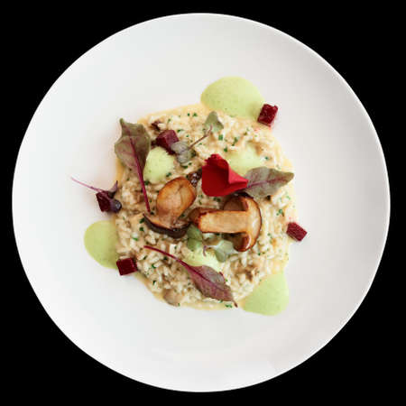 Risotto with fried porcini mushrooms on white plate, isolated on black background with clipping path