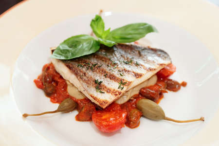 Sea bass fillet with tomato sauce and capers in porcelain plate
