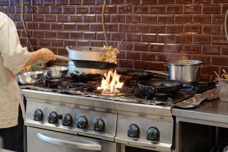 gourmet kitchen: Chef is making flambe dish in restaurant kitchen, motion blur