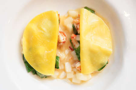 Ravioli-like dish with shellfish, apples and herbs shot from above Stock Photo