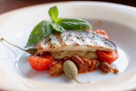 plato de pescado: Sea bass fillet with tomato sauce and capers on white plate Foto de archivo