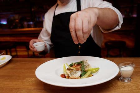 plato de pescado: Chef es la adición de virutas de cebolla fritos con un plato de pescado