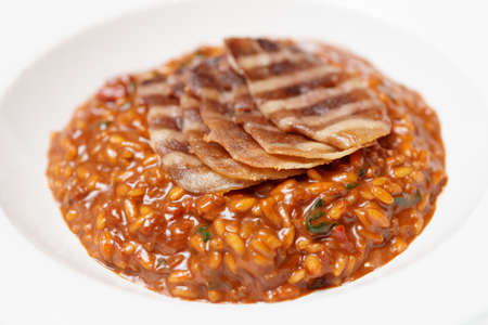Rye risotto with grilled meat slices in deep porcelain plate Stock Photo