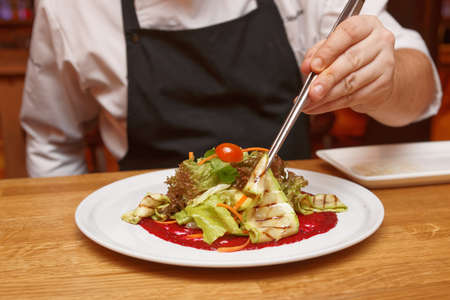 gourmet kitchen: Chef is serving vegetable appetizer with pincers on white porcelain plate