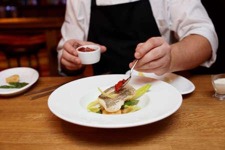 plato de pescado: Chef is adding tomato sauce to a fish dish Foto de archivo