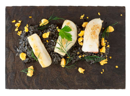Risotto cooked with squid ink, seared calamar on wooden board, isolated on white