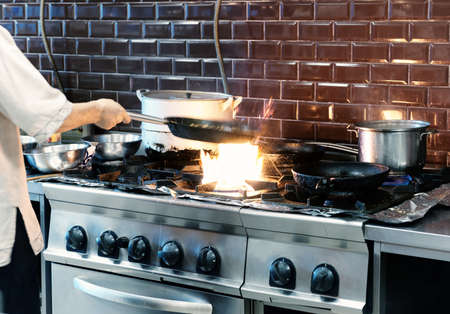 oven range: Chef is making flambe dish in restaurant kitchen, motion blur, toned image