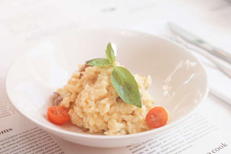 Creamy risotto in porcelain plate served in deep porcelain plate, toned image