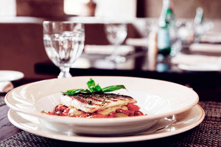 Sea bass fillet with tomato sauce and capers, place setting of a restaurant, toned image Stock Photo