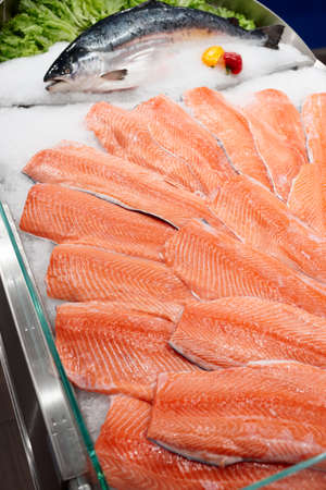 Salmon fillets and whole fish on cooled market display