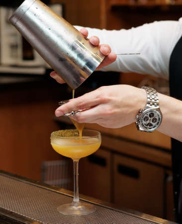 Bartender is pouring cocktail from shaker into a glass Stock Photo