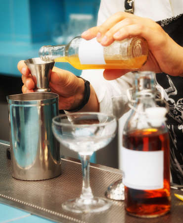 adding: Bartender is pouring homamade infusion into a mixing glass, making cocktail, toned image