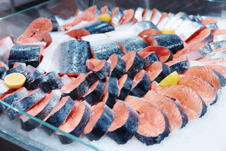 Salmon steaks and fillet on iced food market display, toned image