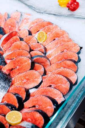 Fresh raw salmon chunks on ice in supermarket or fishmongers shop, toned image